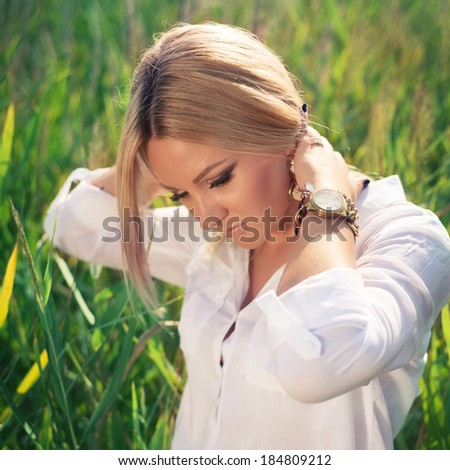 young beautiful woman poses in green thickets, looks in the camera. fashion model - stock photo
