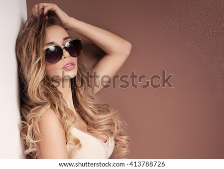 Young beautiful woman posing in mini dress. Studio shot. Long curly hair. Glamour makeup. - stock photo