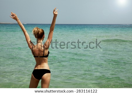 Young beautiful woman posing in water. Summer photo. Sunny day. Girl with slim body.