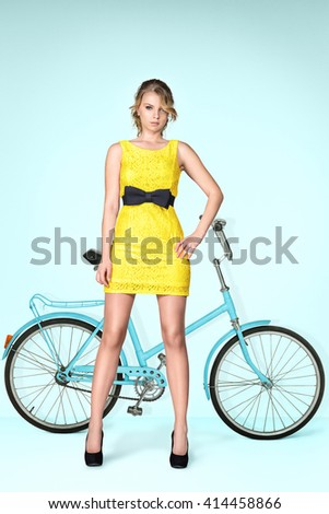 Young beautiful woman posing with old style vintage bicycle. Indoor fashion portrait - stock photo