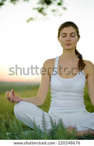Young Beautiful Woman Practices Yoga on the Meadow. Active Lifestyle - stock photo