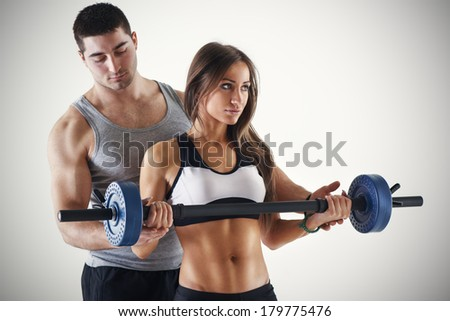 Young beautiful woman practicing Biceps muscle group with personal trainer. - stock photo