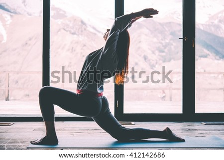 Young beautiful woman practicing yoga with mountain view in the background. Wellness concept. Calmness and relax, woman happiness. Toned picture - stock photo