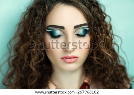 Young beautiful woman, professional art make up blue color, curly hair styling. Pink bright lips. Woman ready for the party or great event. Free space on photo, area place for text inscription, button - stock photo