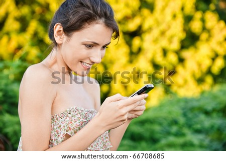 Young beautiful woman read sms by mobile phone, against autumn nature. - stock photo