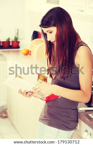 Young beautiful woman reading cookbook in the kitchen, looking for recipe  - stock photo
