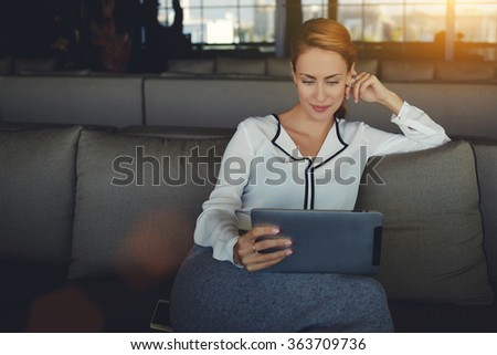 Young beautiful woman reading electronic book via internet on digital tablet while relaxing in coffee shop after work day, modern female watching fashion news on touch pad while waiting order in cafe - stock photo