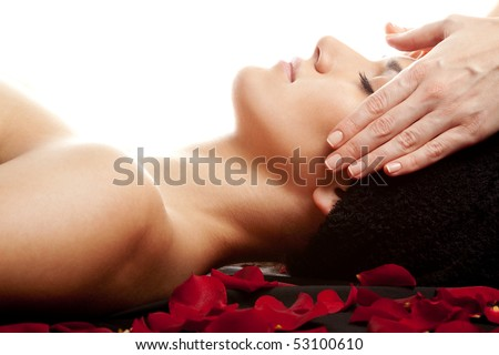 Young beautiful woman receiving a face massage at spa - stock photo