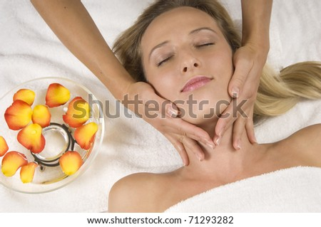 Young beautiful woman receiving a facial massage