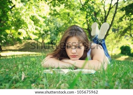 Young beautiful woman relaxing and reading in park - stock photo