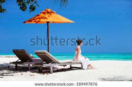 Young beautiful woman relaxing at tropical beach during summer vacation