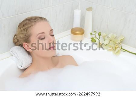 young beautiful woman relaxing in bath with foam - stock photo