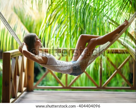 Young beautiful woman relaxing in hammock in a tropical resort - stock photo