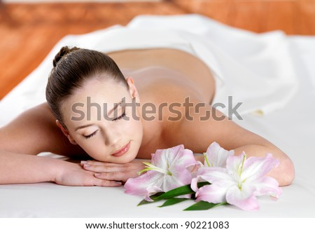 Young beautiful woman relaxing in spa beauty salon - indoors