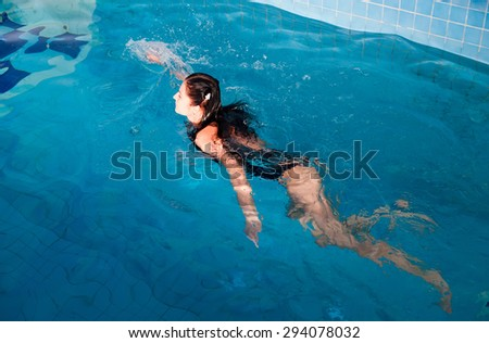 Young beautiful woman relaxing in swimming pool