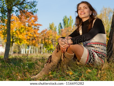 Young beautiful woman relaxing in the autumn park - stock photo