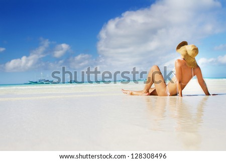 young beautiful woman relaxing on sand beach - stock photo