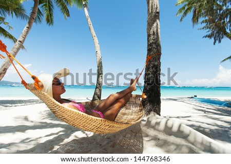 Young beautiful woman relaxing on the hammock - stock photo