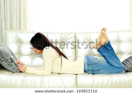 Young beautiful woman resting on a sofa with tablet computer at home - stock photo