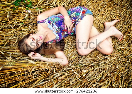 Young beautiful woman resting on golden wheat - stock photo