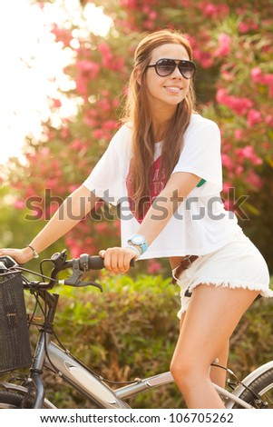 Young beautiful woman riding bicycle on summer - stock photo