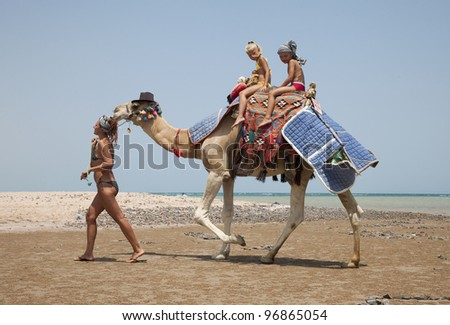 Young beautiful woman rolls the children on a camel on the beach