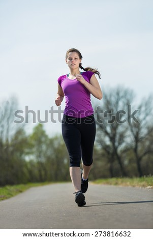 Young beautiful woman runner doing jogging path for success for a healthy lifestyle in natural landscape. - stock photo