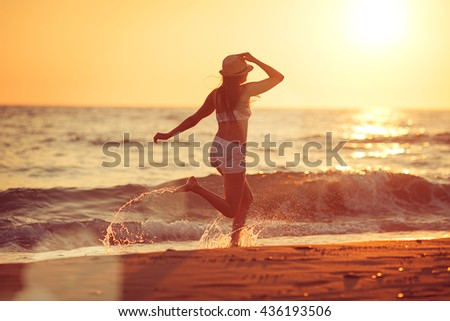 Young beautiful woman running barefoot in the surf on the sand beach at sunset; lens flares