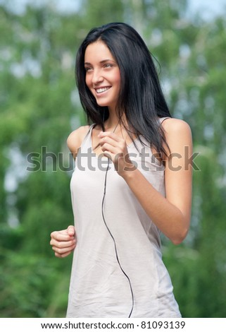 Young beautiful woman running in park and listening to music - stock photo