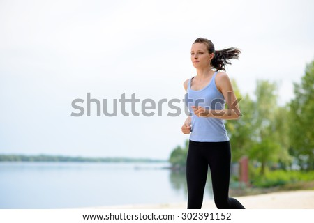 Young Beautiful Woman Running on the Beach Trail in the Morning. Active Lifestyle - stock photo