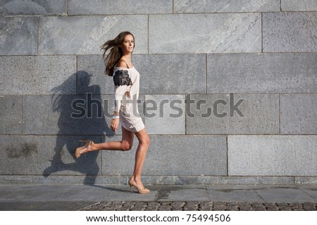 Young beautiful woman runs against a stone wall