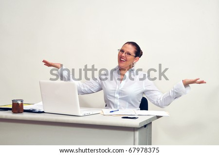 Young, beautiful woman seated at her desk behind her laptop with both arms extended in an open, welcoming gesture