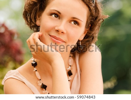 Young beautiful woman sits at little table in summer cafe. - stock photo