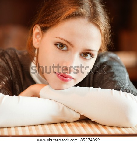 Young beautiful woman sits in cozy cafe and looks. - stock photo