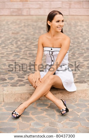 Young beautiful woman sits on stone step in street cities.