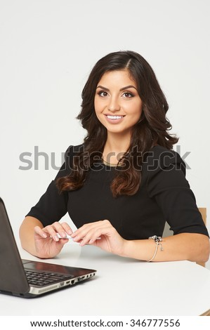 Young beautiful woman sitting at a desk in the office. next to her laptop. Her dark long hair, white teeth, she smiles. - stock photo