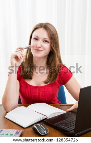 Young beautiful woman sitting at the table with a laptop, notebook, mouse and calculator with  pen in her hand. Looking at the camera and smile - stock photo