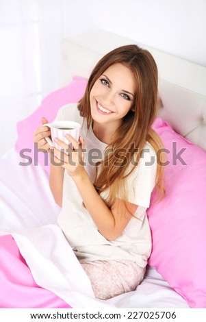 Young beautiful woman sitting in bed with cup of hot drink - stock photo