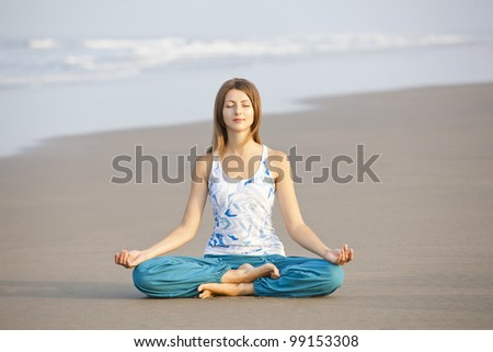 Young beautiful woman sitting in meditation pose on the beach