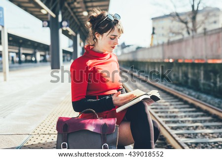 Young beautiful woman sitting on a platform in a train station reading a book- student, commuter, reading concept - stock photo