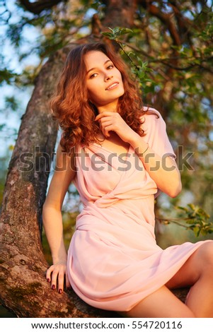Young beautiful woman sitting on a tree in blooming gardens (selective DOF)