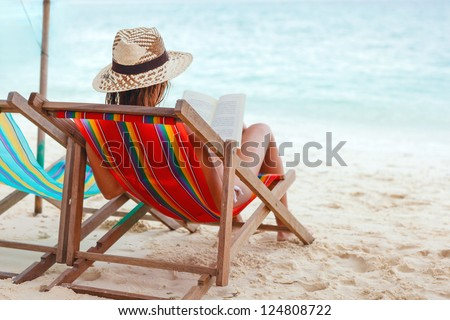 Young beautiful woman sitting on beach reading a book - stock photo
