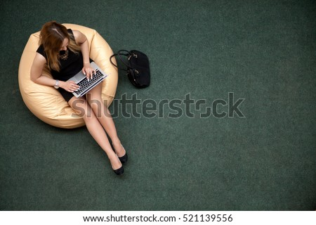 Young beautiful woman sitting on bean bag working on laptop in public wifi area, typing, top view, copy space. Green carpet on the background floor. Full length