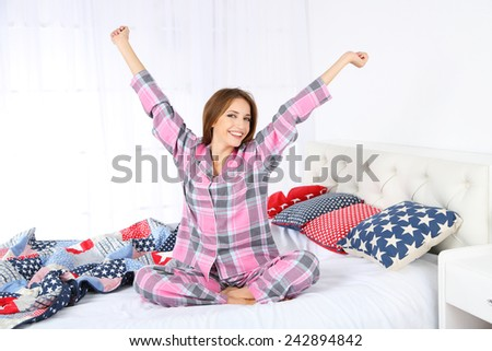 Young beautiful woman sitting on bed  - stock photo