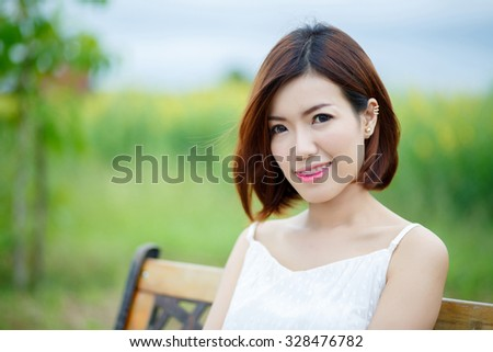 Young beautiful woman sitting on bench in park. - stock photo
