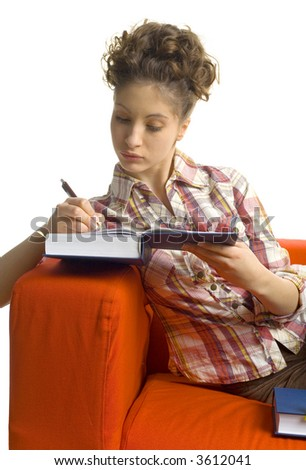 Young, beautiful woman sitting on orange couch. Writing on book.  White background - stock photo