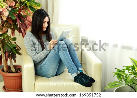 Young beautiful woman sitting on the armchair with tablet computer at home - stock photo