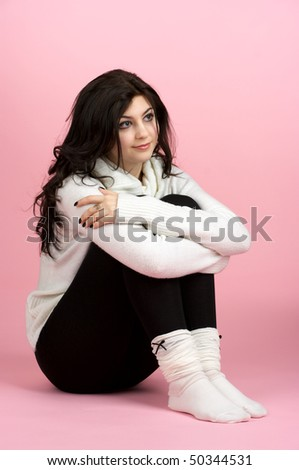 Young beautiful woman sitting on the floor over pink background - stock photo
