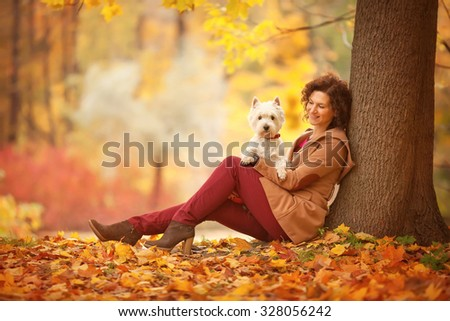 young beautiful woman sitting under the tree and  holding her white small dog on the hands in the autumn park  - stock photo