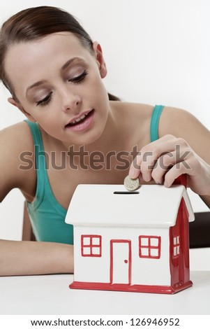 young beautiful woman sitting with  model house piggy bank,  real estate concept. - stock photo